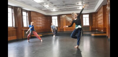 Three dancers in a wood panelled studio with a black floor.  They make angular shapes with this bodies